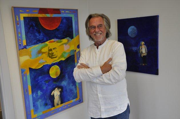 FARGESTERKT: Per Helge Hansen med to av sine bilder på utstillingen. De sterke fargene går igjen.
