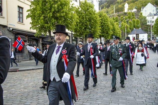 Bergen er blitt kjent for lange sløyfer og flosshatter med 17. mai-komiteen fremst i prosesjonen. Her er morgenprosesjonen på nasjonaldagen i fjor med komiteens formann Erik Næsgaard fremst. FOTO: EIRIK HAGESÆTER