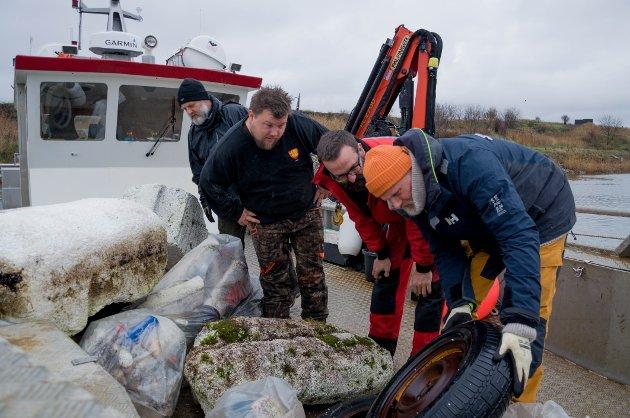 Et tipp topp bildekk er blant søppelet i naturreservatet. Bak fra venstre friluftsrådgiver Pål Erik Jensen fra Østfold fylkeskommune, Hans Nordskog og Thomas Warren Eriksen fra Skjærgårdstjenesten og Sten Helberg fra Kystlotteriet.