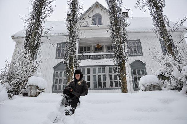 STASELIG: Grete Halvarda Hartvigsdatter i hagen med ospetrærne foran det gamle bankbygget fra 1914.