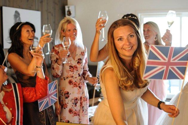 GOD STEMNING: Ann Kristin Åslid (bak til venstre) inviterte mange venninner til bryllupsfest med rosa sjampanje, store plakater med Meghan og Harrry og så klart britiske flagg.