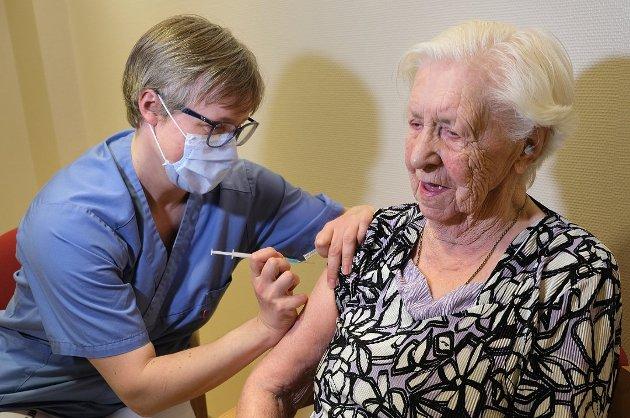 FØRSTE STIKK: Judith Sollied (98) var den første som fikk korona-vaksinen i Senja kommune. Sykepleier Cecilie Halsnes setter sprøyten.