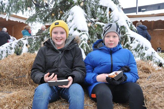 """KOSTE SEG: Lukas Raknerud Torkildsen (11) og Oskar Skjør Arntsen (11) spise kyllingklubber og hygget seg under arrangementet """"Jul i bygda"""" på Skjønhaug torg."""