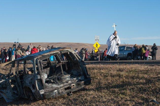 Kirkesamfunn deltar i protestene mot oljeledningen the Dakota Access pipeline. Bildet er tatt torsdag og viser engeistlig som passerer et utbrent bilvrak.