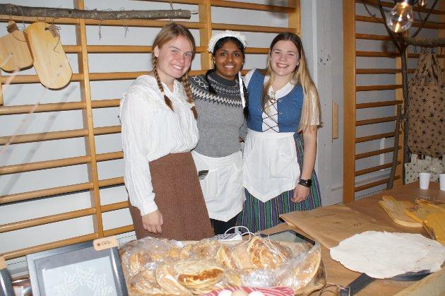 Smilende jenter i salgsbua Joanna, Abinaya og Julia.