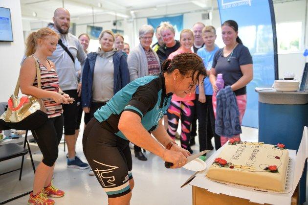 Kakedags: Elisabeth Melby Hagen skjærer det første stykket av jubileumskaka mens medlemmene står klare til å få hvert sitt stykke, velfortjent, etter ei hard treningsøkt.