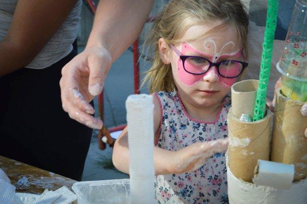 Jennie Malaika Gjervoldstad (5) koser seg på gatefest. Her lager hun kunst av plast og diverse småtteri.