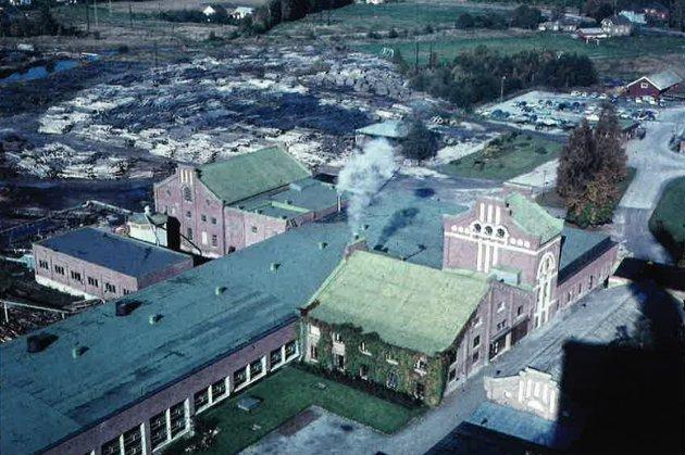 I 1964: Bildet er tatt fra taket på Sande Paper Mill i 1964, og viser alt grantømmeret til Sande Tresliperi, og fotballbanen til Selvik IF. Legg også merke til den røde saga, som ligger nord for parkeringsplassen. Nede til høyre er verkstedbygningen, som var det siste som ble revet.