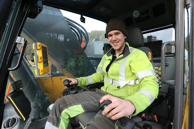 Gravemaskinfører Jonas Rønningen (24) fra Risør smiler bak spakene i førerhytta på gravemaskinen sin. Helt siden de første tennene på gravemaskinskuffa ble satt i Vormeliveien 1. september i fjor, har han jobbet med veiprosjektet for entreprenøren Knut haugsjå AS.