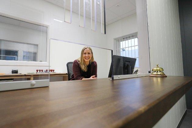 Politiets samfunnskontakt i Risør og Gjerstad, Margrethe Solvang, smiler i luka. Her kan publikum plinge i bjella når de ønsker kontakt: – Vi kommer til å ha åpent to dager i uka i første omgang. Da vil det alltid være noen tilstede i nærheten av luka. Utenom åpningstidene er det bare å ringe på dørklokka, eller avtale en time.