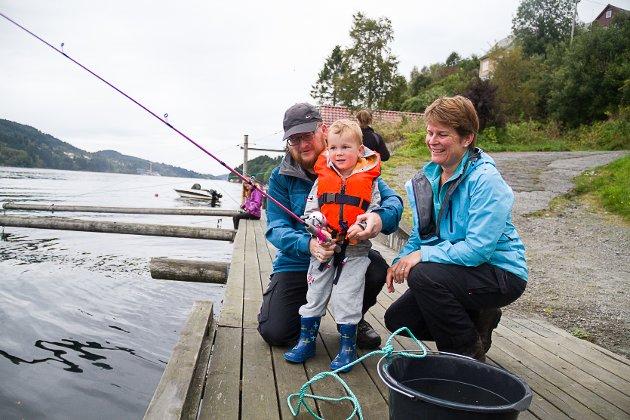 BARNAS FISKEDAG: Tore Kalnes, Eivind Smith Kalnes (4) og Grethe Kalnes fekk høyra om Barnas fiskedag via naboar. – Vi har aldri vore med på dette før, men synest det var veldig kjekt, det er eit flott tiltak. Eg trur vi kjem att neste år, seier pappa Tore.