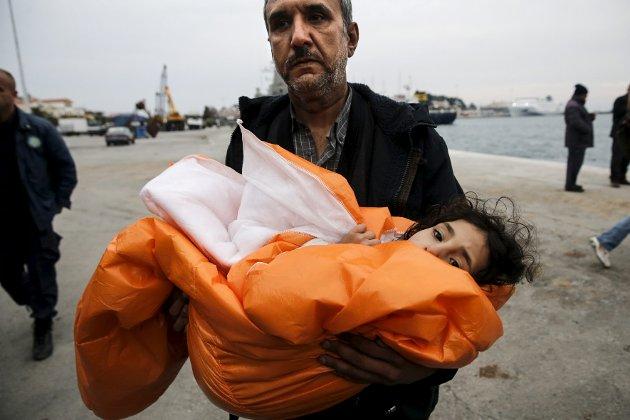 En syrisk mann bærer datteren sin i et teppe etter å ha blitt reddet i Egeerhavet.