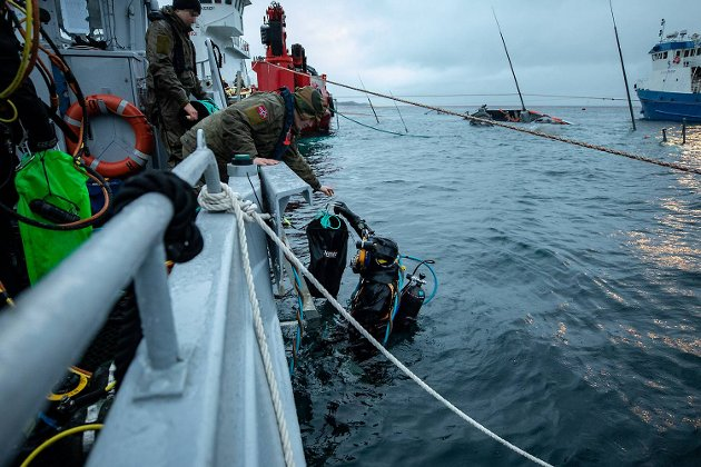 En minedykkeroperatør langer verktøy i et nett til sin kollega i dykkerutstyr som skal ned for å demontere NSM.