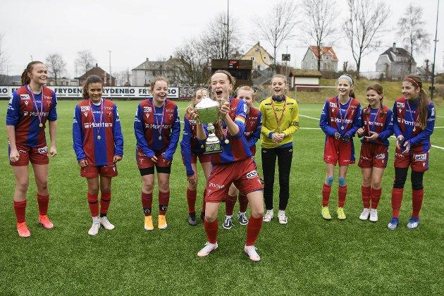 Smørås-jentene har ikke spilt tellende fotballkamper siden oktober i fjor.      Denne helgen ble J15-laget endelig «sluppet fri». Her løfter kaptein Matilde Birkenfeldt (14) pokalen etter finaleseier mot Baune. – Vi har mange andreplasser, men nå vant vi endelig, jubler hun.
