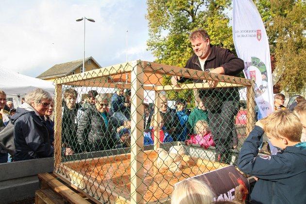 HØNSEBINGO: Høstmarken-pådriver Jan Helge Havsø plasserer høna i buret, og nå er det klart for hønebingo. Rundt buret står ivrige gamblere. Kommer høna til å gjøre sitt fornødne på deres lodd-nummer?