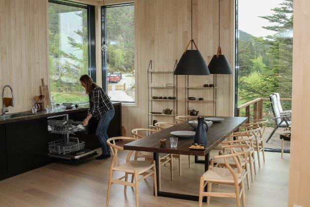 Kristine Offerdal på kjøkkenet. Det store rommet er lyst, med god takhøgd, og har vindauge mot aust og dei andre hyttene. Bordet kan dekkast til 12 personar.