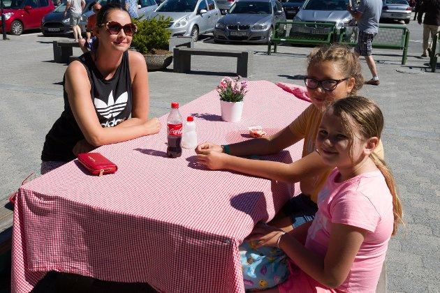 Grethe Helle og borna Violet Sahiti Helle (11) og Valentina Sahiti Helle (7) nyt sola på torget i Førde. – Vi har kjøpt oss jordbær og kosar oss medan vi ventar på bror min, fortel Grethe.