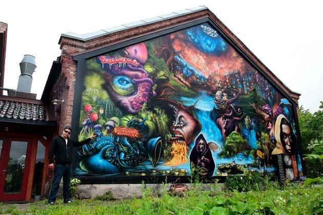 """Grafittikunsteren Stubberud startet med hiphop på St. Croix-huset for over 20 år siden. Veggmaleriet """"Save the planet"""" dekker nå en hel vegg på baksiden av aktivitetshuset. Foto: Ole-Morten Vestby, 17. juni 2011"""