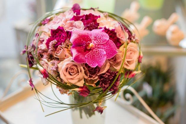 Bukett i lilla og rosa toner. Den lilla tonen med litt grått i er veldig populær for tida. Blomsten er satt sammen av bruderoser, nelliker, en orkidé og bjørnegress rundt.