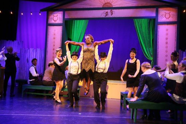 – Tivolihaven har sine ord i behold, den store forestillingen er definitivt en vellykket musikalkomedie, og det svært omfattende ensemblet, med over tretti skuespillere, dansere og musikere på scenen, er i sannhet hardtarbeidende, skriver vår anmelder. På bildet blir Josephine Baker, i   Kim Fairchilds skikkelse, løftet frem.