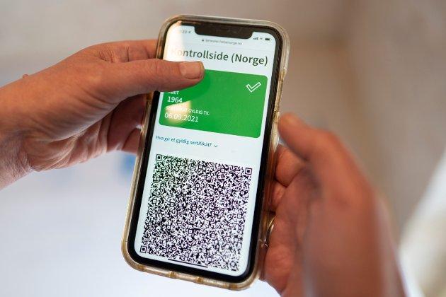 FHI har kommet med et nytt koronasertifikat, der en QR kode i en mobil applikasjon viser om en person er fullvaksinert. Foto: Heiko Junge / NTB