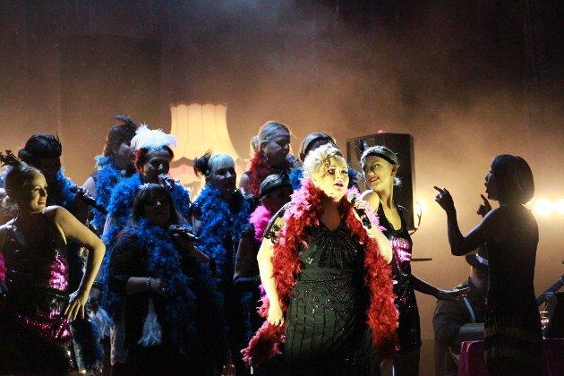 Det ble en spenstig forestilling med mange fengende melodier da Club Diva hadde urpremiere fredag kveld. Her er Marie Huske Mikalsen Isvik i en av sine solistroller, flankert av dansere Miriam Sørhus og Maja Hoen Iversen. Dirigent Siv Cathrine Johansen til høyre i bildet.
