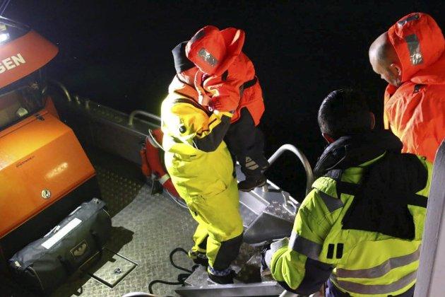 «Pluggen»: Passasjerene hjelpes over fra «Fløttmann» til lettbåten «Pluggen» for å komme seg i land i Beisfjord. I og med at det ikke finnes en kai å legge til må passasjerene fraktes i en mindre båt det siste stykket til land. Bildet er tatt rett etter klokken 0230 natt til tirsdag 3. desember, 12 timer etter at et skred stengte Beisfjordveien.