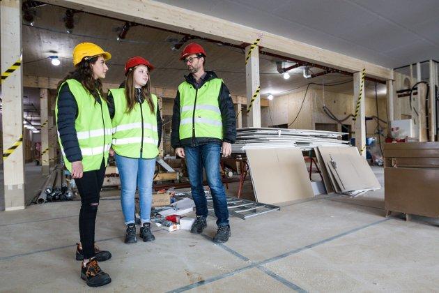 Rektor, Jørgen Bo Gundersen har med seg eleven Sandra Obniska (rød hjelm) og Dina Muhanna (gul hjelm) på en omvisning på den nye ungdomsskolen på Tråstad.