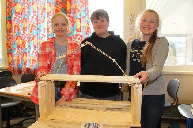 """Workshop om trekonstruksjoner på 7. trinn ved Langeland skole. Thea Gjølstad (t.v.), Sondre Holen og Ella Bø Lysømes med brua """"Glomma est""""."""