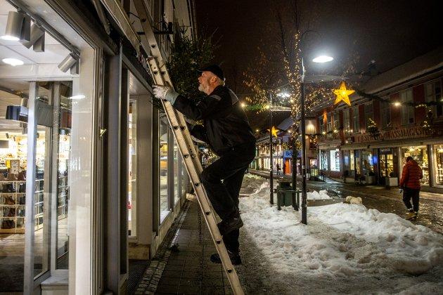 Helge Haugen setter opp et lite juletre på en av fasadene i gågata. Til sammen har veterankorpset satt opp 99 slike trær i løpet av søndagen.