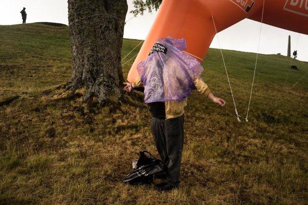 """1. En mann tar på seg regnponchoen sin da himmelen åpnet seg. På ponchoen står det """"kill the rain not the fun"""".  Jeg liker bildet fordi det visuelt funker veldig bra, mye på grunn av at fargene spiller fint sammen. Samtidig er det en litt komisk situasjon, hvor hodet ikke helt har funnet veien sin ut åpningen. Dette bildet av regn representerer store deler av festivalens værforhold."""