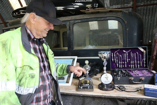 Håkon Hansen viser frem noen av prisene den nyinnkjøpte ambulansen, en Opel kaptein, har vunnet.