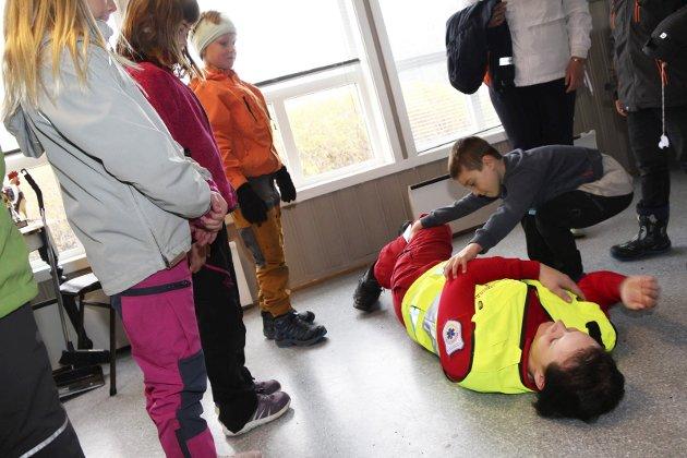 Lion Drezewicz har stålkontroll når han legger amulanselærling SiWWassdal Sollie i sideleie. Onsdag sørget nødetatene - brann, politi og ambulanse - for at 2. klasse ved Kulstad skole fikk lære førstehjelp.