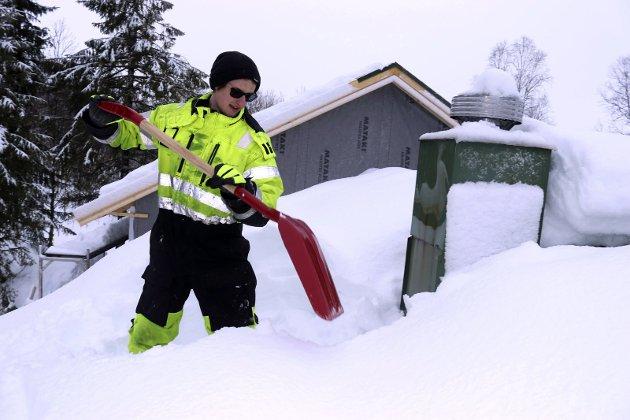 grynne i snøen: Grane hytteservice AS tar oppdrag med alt fra snekring til snømåking. Det rapporterer om store lokale forskjeller i Fiplingdal, med 2,30 meter på Endresplass mot 1,5 meter i Simskaret. Her er Joar Inemyr (18) klar for innsats på hyttetaket. Foto: Stine Skipnes