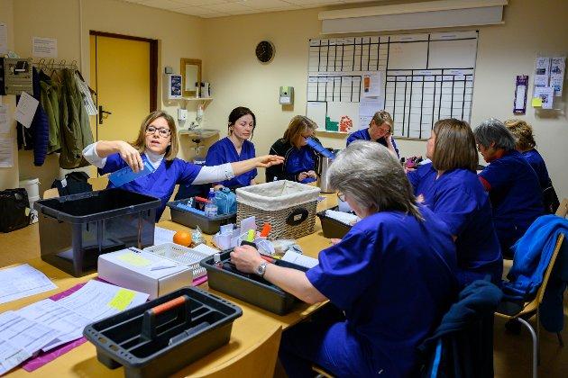 Ferdig doserte medisiner deles ut og puttes i medisinkurver. I dag er det Kari Janne Gladsø som deler ut medisin til 11 pleiere som snart skal ut til mellom 10 og 20 bruker hver. Praten rundt bordet dreier seg om brukerne og det som virker kaotisk, har allikevel form. Dette er effektive damer som utnytter hvert øyeblikk og de hjelper hverandre med å holde oversikten over de rundt 120 brukerne i kommunale og private boliger.