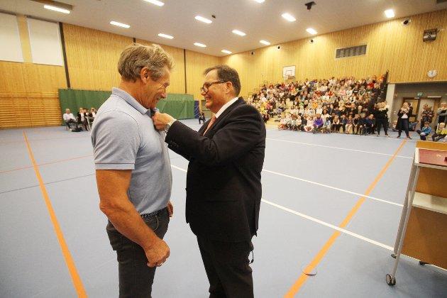 Fylkesmann Per Arne Olsen fester medaljen på Harald Sando.