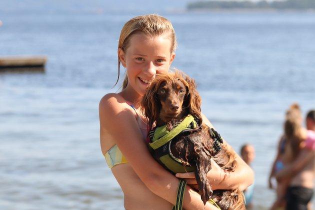 Tuva (11) med hunden Emil (1). – Det er så varmt, så Emil måtte også bade, forklarer Tuva. Hun koser seg de siste feriedagene, men gleder seg også til å begynne i 7. klasse til uka.