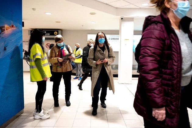 SMITTEVERN: Tromsø kommune og korona-teamet informerer passasjerer i ankomsthallen på flyplassen om smittevern i kommunen, blant annet krav om testing.