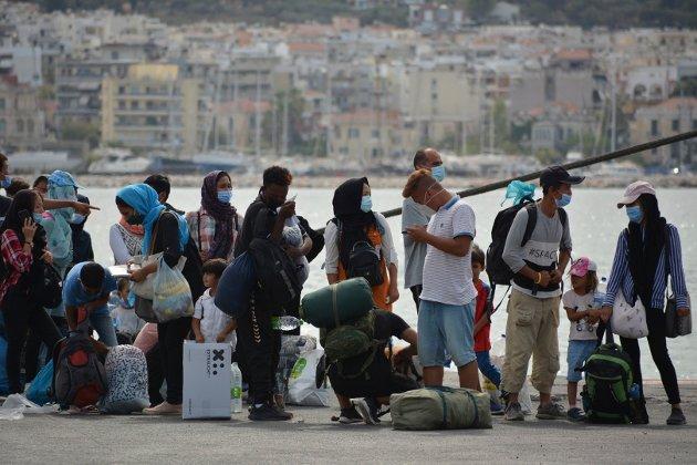 Flyktninger i kø for å bli ført vekk fra øya Lesbos etter brannene i Morialeiren i september 2020.