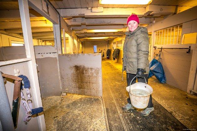 TUNGE LØFT: Stallmester Hege Moen bærer bøtter fulle av vann til de mange hestene som venter på å komme inn i stallen.