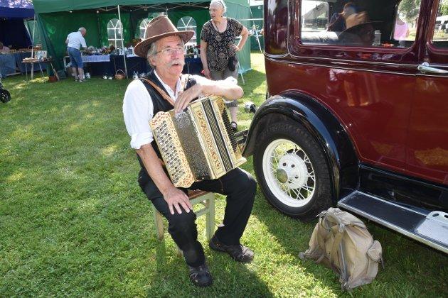 TRUBADUR: Jan Karlsen har bosatt seg i Osen og litt rundt omkring på Osendagene, mest der han finner skygge, for trekkspillet tpler ikke mye sol. Bilen er også hans. En A-ford fra 1931. – Det er fint å ha et arrangement der alle samles, sier han.