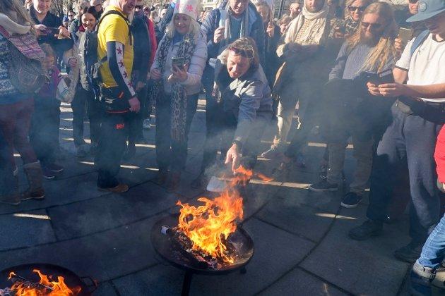 DEMONSTRERER: Svein Østvik (Charter-Svein) brenner munnbindet sitt under koronaskeptikernes markering utenfor Stortinget lørdag ettermiddag.
