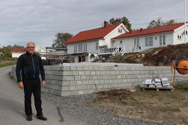 Tormod Eek ved den nye støttemuren på eiendommen til Sandøya Handelshus og bistro, og bolighuset deres. Området er planert ut og skal få belegningsstein.