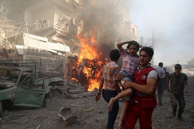 SYRIA: Hjelp til de borgerkrigsrammede i Syria står på agendaen hos mange hjelpeorganisasjoner. På bildet bærer en Røde Halvmåne-ansatt ei jente vekk fra et bombeangrep. (Foto: Bassam Khabieh / NTB scanpix)