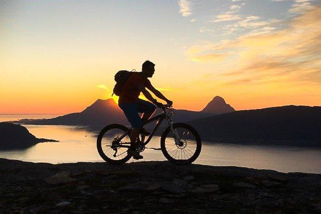 Bildet viser en syklist oppå Nesnakjølen en fin sommerdag.