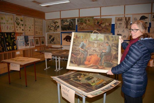 Plansjer i en rekke utgaver selges fra de to skolene. Her viser Hilde Horten fram plansjer under kategorien arbeidsyrker.