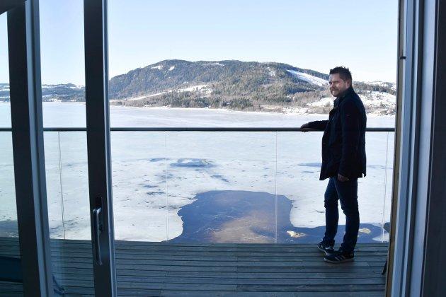 UTSIKT: Eiendomsmegler Morten Iversen på terrassen til leiligheten i 16. etasje, der man kan skue utover Furnesfjorden. – Jeg tror ikke man finner noen bedre utsikt mot Mjøsa enn dette, sier Iversen.