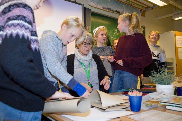 IVRIGE: Elin Jannicke Ihler er lærer i kunst og håndtverk, og storkoser seg i sjuendeklasse. Elevene Frank Werner Laug, Aurora Alina Thronæs og Andrine Kramer Fønhus har fått i oppgave å lage et bokomslag.
