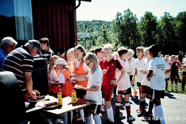 Pensjonistene Kai Sivertsen og Birger Bech serverer sultne fotballentusiaster grillmat.