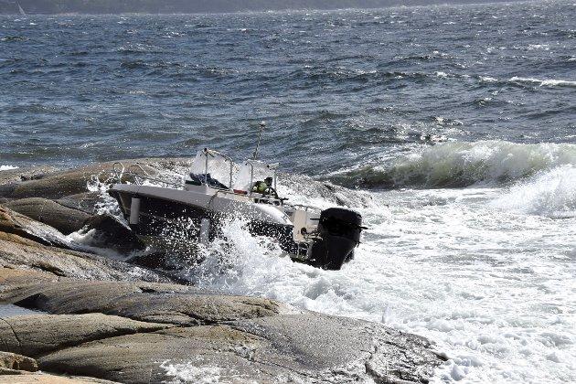 Båten lå og slo i fjæresteinene.